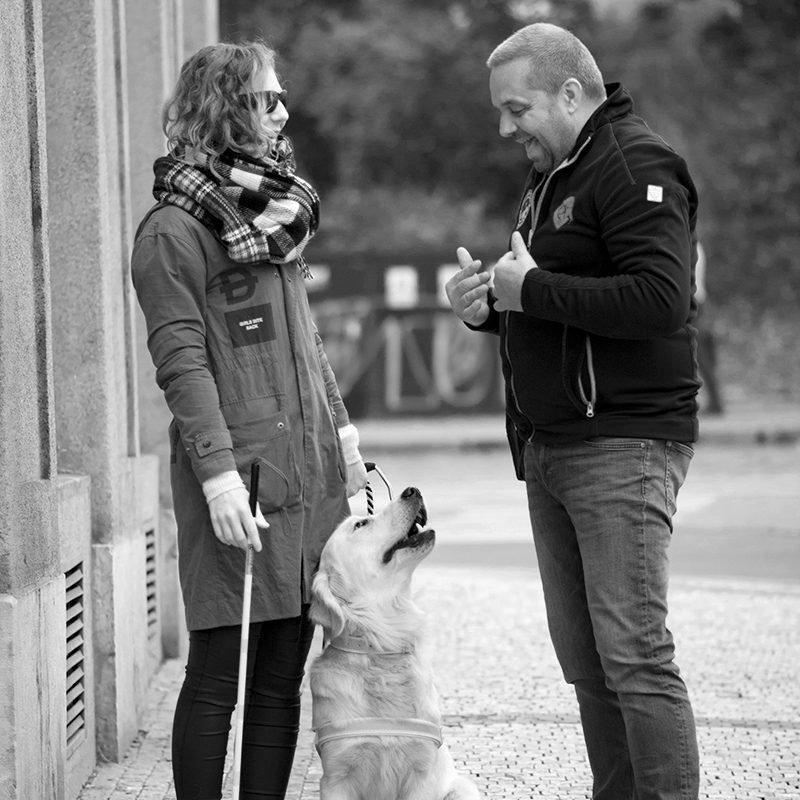 Zpěvačka Lenny doprovázená vodícím psem diskutuje s kolemjdoucím