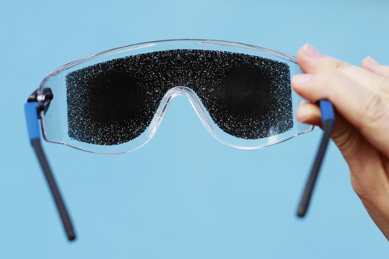 Ruka drží brýle se začerněnými skly.