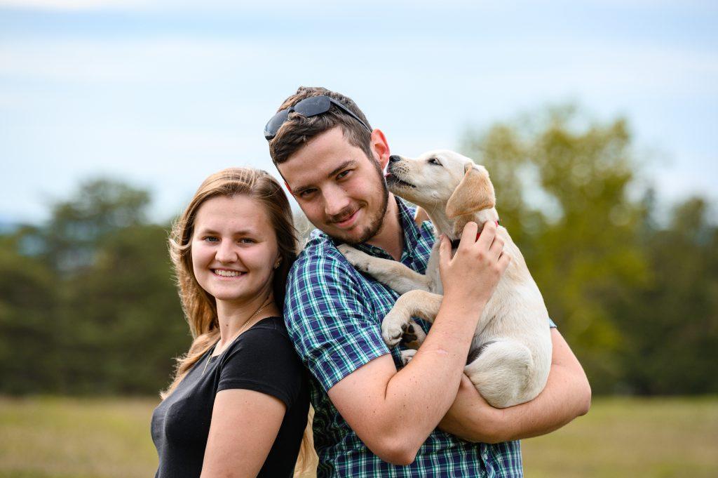 Mladý pár stojí na louce a usmívá se, muž drží v náručí štěně, které mu olizuje tvář.