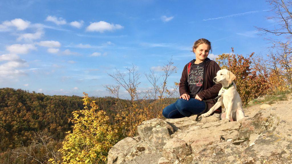 Mladá žena a retrívr sedí vedle sebe na skále. V pozadí jsou vidět vrcholky stromů z přilehlého lesa.