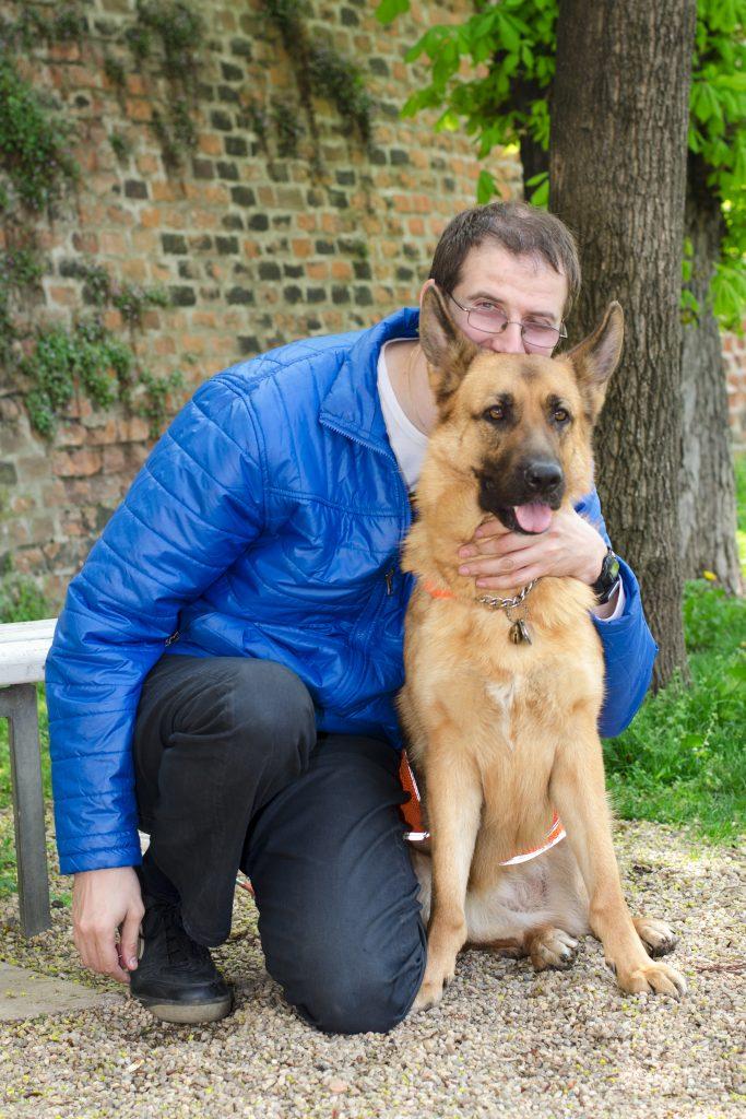 Německý ovčák sedí na zemi, vedle něj klečí muž v bundě a džínách, který dává psovi pusu mezi uši.