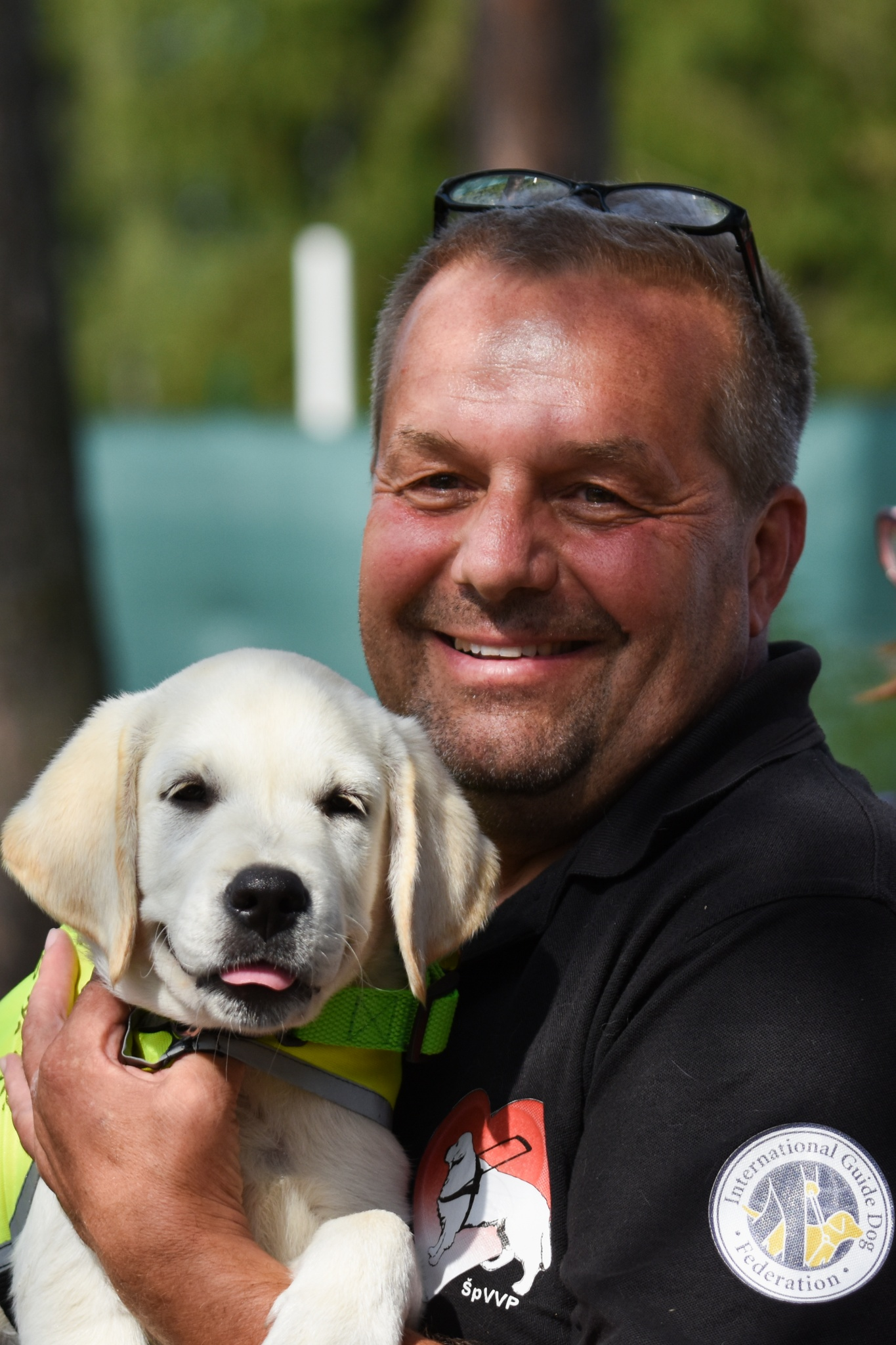 Muž ve středním věku se směje do kamery a drží v náruči štěně s vestou vodicího psa ve výcviku.