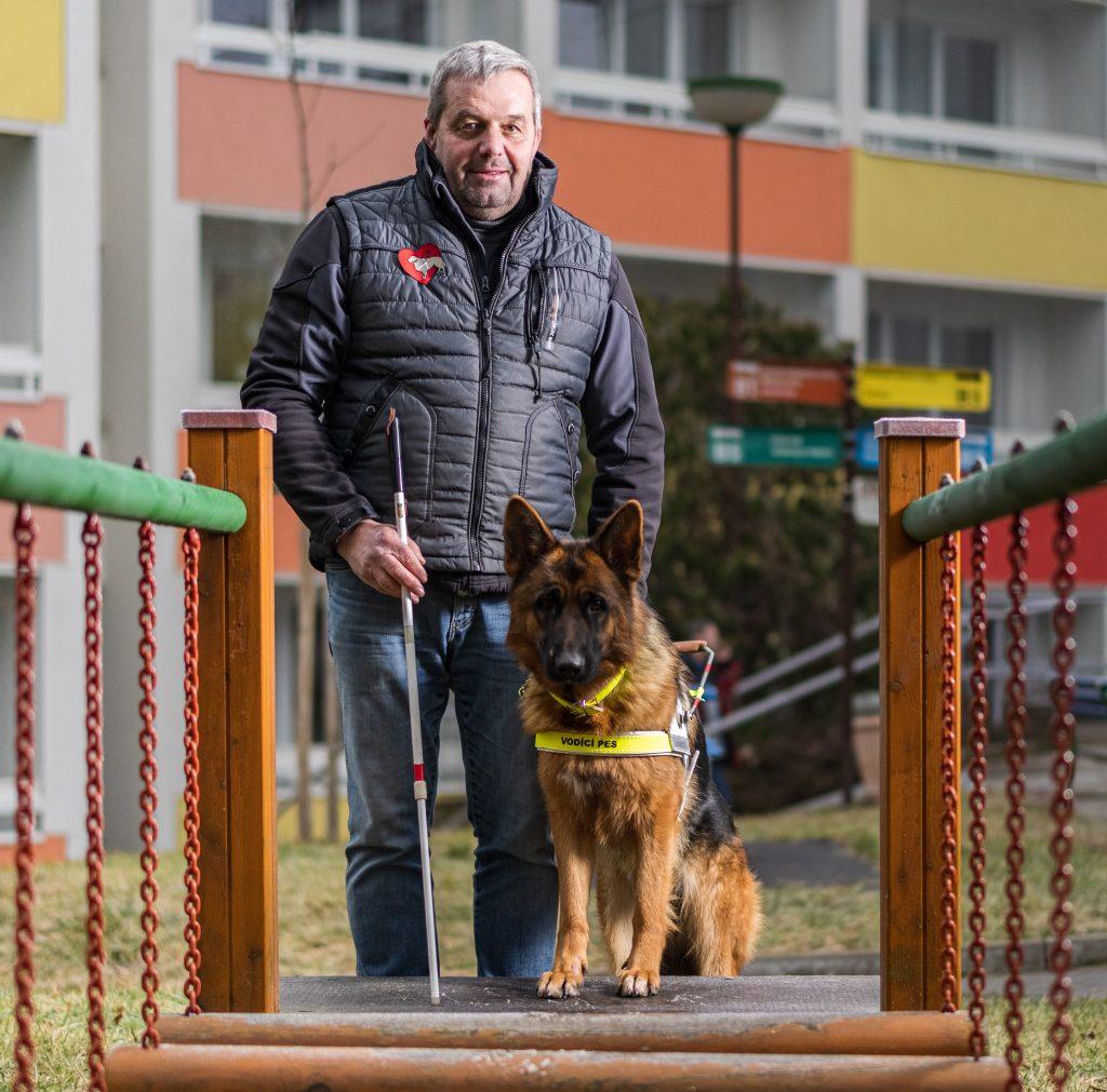 Muž stojí na kraji visutého mostu, drží v ruce bílou hůl a u nohou mu sedí německý ovčák v postroji vodicího psa.